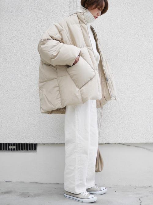 ホワイトダウンジャケットとホワイトタートルネックセーターにホワイトテーパードデニムを履いた女性