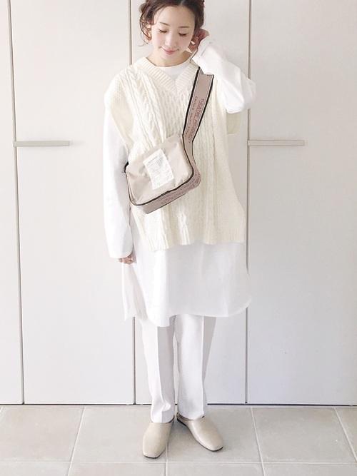 ホワイトケーブルニットベストとホワイトレイヤードインナーにホワイトテーパードパンツを履いた女性