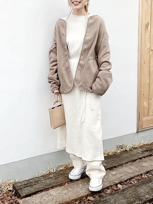 ホワイトラップワンピースとホワイトストレートデニムにホワイトスリッポンを履いた女性