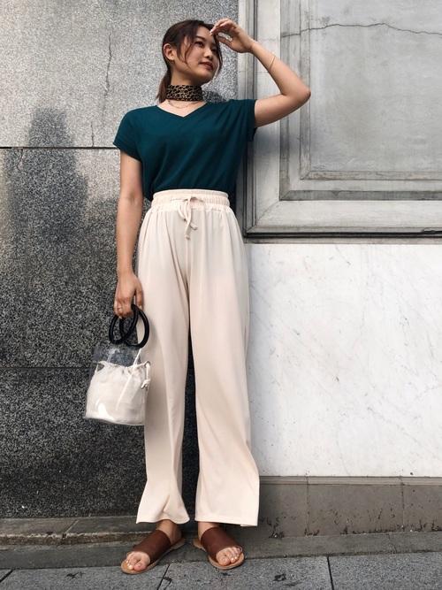 GUのVネックトップスとプチプラ通販のイージーパンツにヒョウ柄スカーフを履いた女性