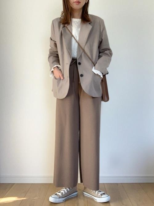 フラワーレースブラウスとテーラードジャケットにリラックスパンツを履いた女性
