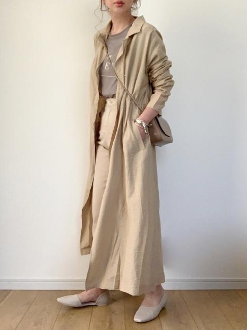 トレンチコートとコットンワイドパンツにパンプスを履いた女性