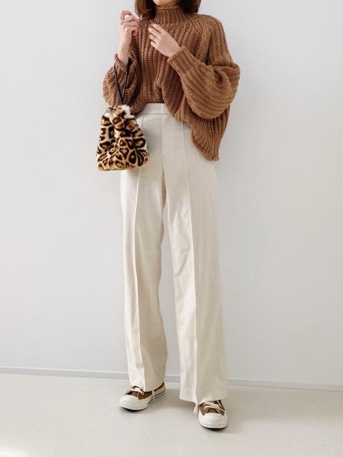 H&Mのローゲージセーターとユニクロのハイウエストワイドパンツにフェイクファーバッグを持った女性