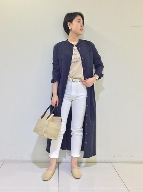 ヒューマンウーマンのシャツワンピースと白ロゴTシャツにホワイトデニムパンツを履いた女性