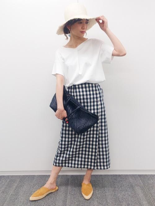 スキッパーカットソープルオーバーとチェック柄ラップスカートにヒューマンウーマンのレザーメッシュバッグを履いた女性