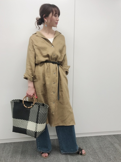 ベージュリネンシャツワンピとワイドデニムパンツにヒューマンウーマンのビニールかごバッグを履いた女性