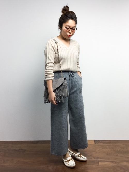 ベージュVネックニットセーターとグレーニットクロップドパンツに白デッキシューズを履いた女性