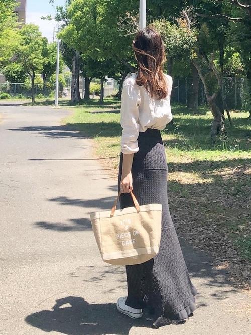 グレー透かし編みニットタイトスカートとベージュリネンシャツにベージュトートバッグを履いた女性