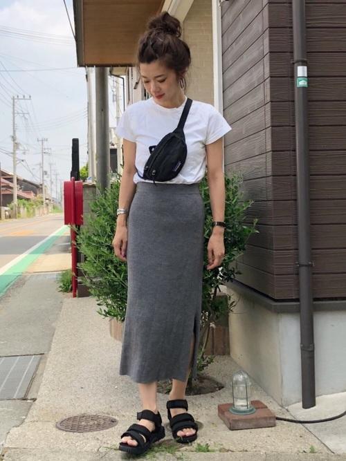 グレーリブタイトスカートと白キャップスリーブTシャツに黒スポーツサンダルを履いた女性