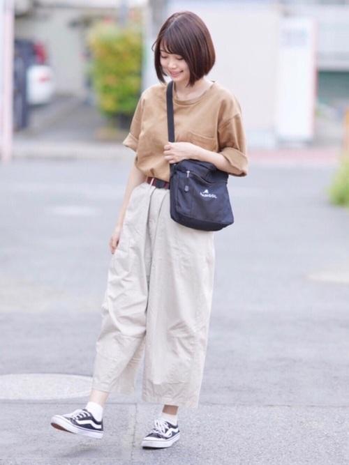 カンゴールのショルダーバッグとベージュTシャツにワイドチノパンツを履いた女性