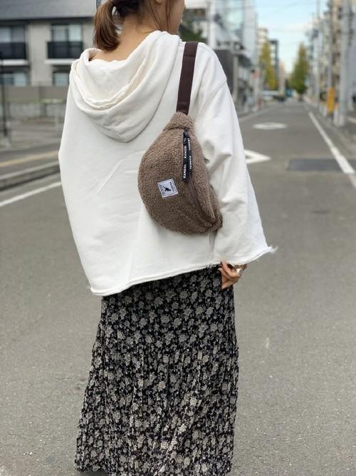カンゴールのウエストポーチとホワイトパーカーに花柄スカートを履いた女性