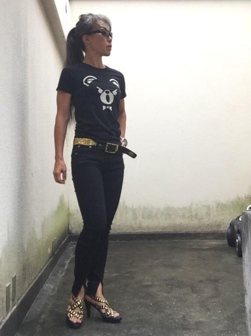 ロックTシャツとブラックスキニーデニムにゴールドスタッズサンダルを履いた女性