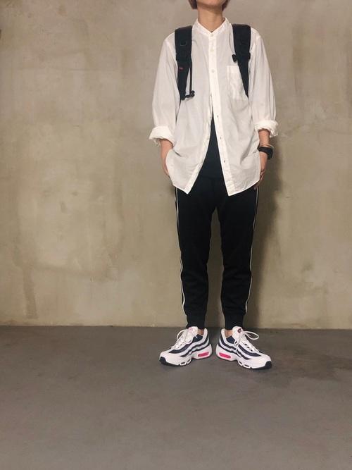 ナイキ黒サイドラインジョガーパンツと白ソフトツイルスタンドカラーシャツに白スニーカーを履いた女性