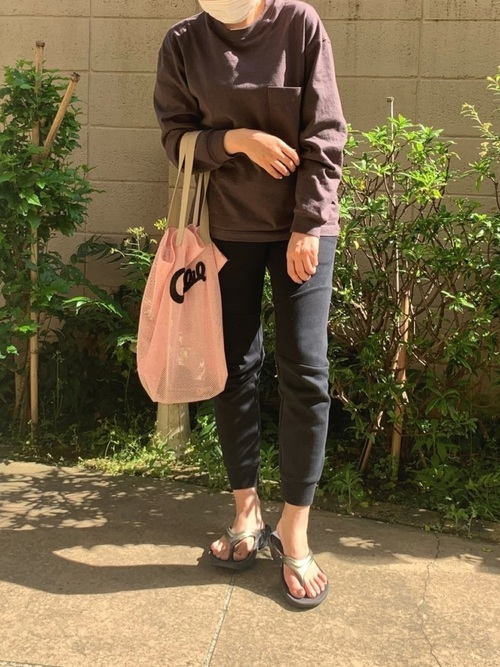 ナイキ黒テックフリースジョガーパンツとブラウンクルーネック長袖Tシャツに黒トングサンダルを履いた女性
