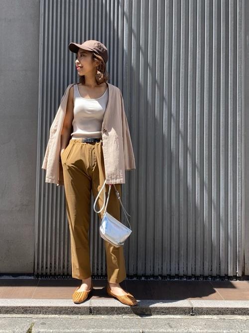 Vネックシャツジャケットとホワイトタンクトップにストレッチパンツを履いた女性