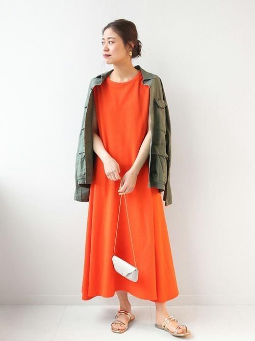 ミリタリーシャツジャケットとコットンマーメイドラインワンピースにフラットサンダルを履いた女性