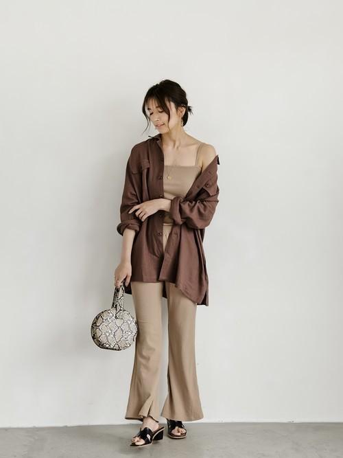 リネンルーズサファリシャツジャケットとブラウンキャミソールにフレアパンツを履いた女性