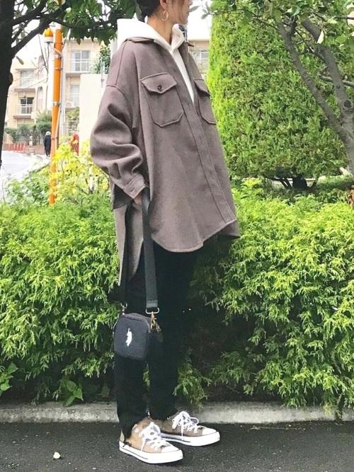 ブラウンシャツジャケットとIラインフーディにデニムパンツを履いた女性