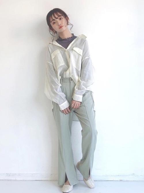 白シアーシャツとチュールカットソーにミントグリーンパンツを履いた女性