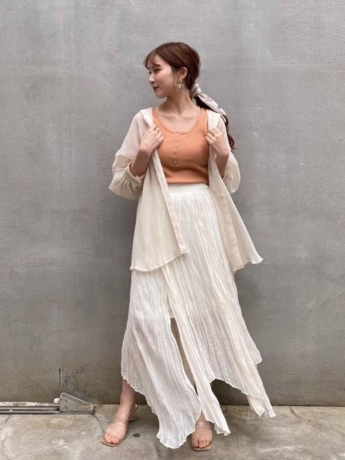 ベージュ八分袖シャツとオレンジタンクトップにワッシャ―フレアスカートを履いた女性
