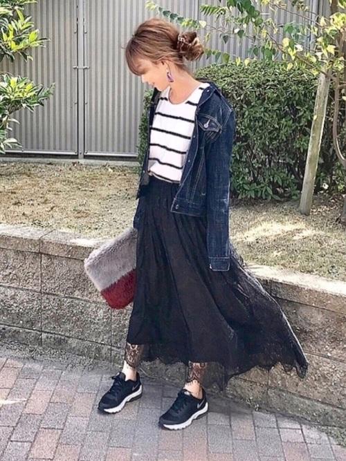 ファーバイカラークラッチバッグとウォッシュドデニムジャケットに黒レーススカートを履いた女性