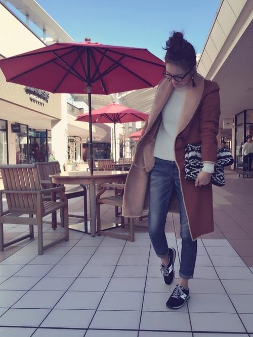 ネイティブジャガードクラッチバッグとムートンロングコートに黒ローテクスニーカーを履いた女性