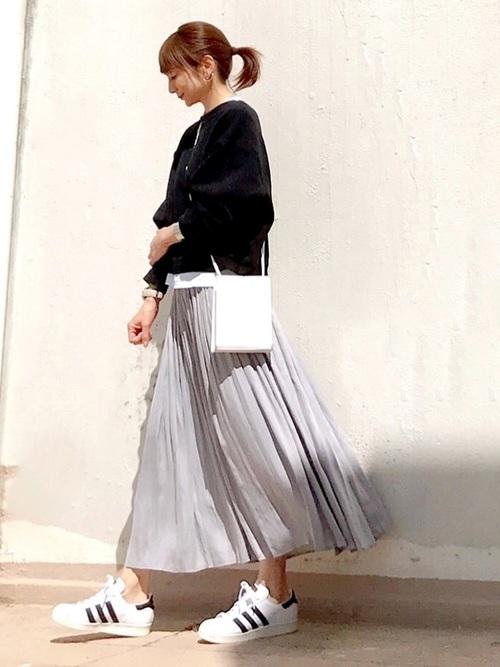 黒ショート丈スウェットプルオーバーとグレープリーツスカートに白スニーカーを履いた女性