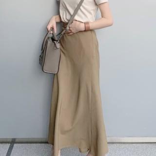 ユニクロのベージュTシャツにベージュのロングスカートを履いた女性