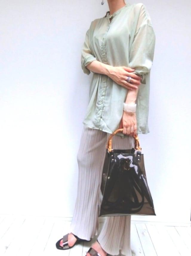 しまむらのグリーンのシアーシャツにプリーツパンツを合わせた女性