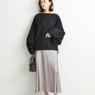 ボートネックビックシルエットシャツにグレー系スカートを履いた女性