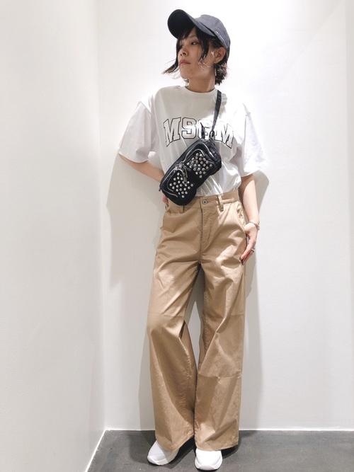 :白Tシャツとベージュチノパンと白アトランティックスターズを履いた女性