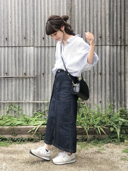GUの濃紺デニムタイトスカートとライトブルーストライプシャツに白スニーカーを履いた女性