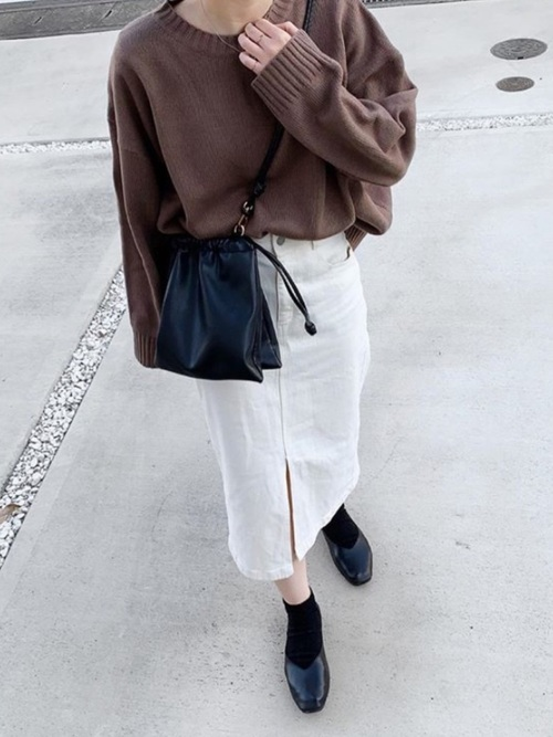 GUの白フロントスリットデニムタイトスカートとブラウンクルーネックニットに黒甲深Vカットフラットパンプスを履いた女性