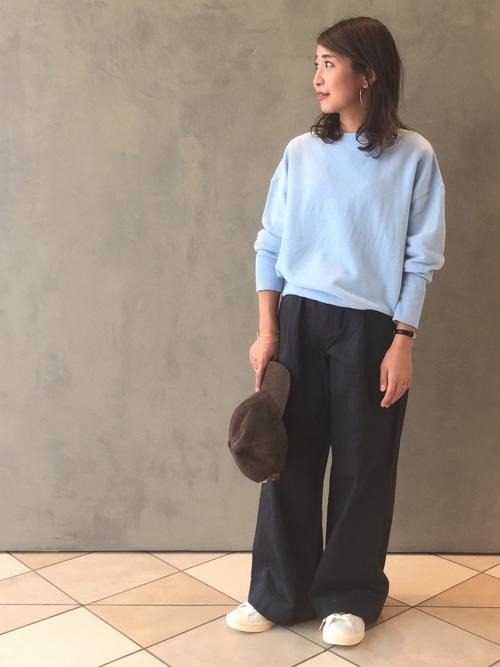 ライトブルーコットンウォッシュスウェットプルオーバーにグレーワイドチノパンツを履いた女性