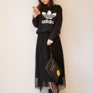 黒スウェットトレーナーにチュールプリーツスカートを履いた女性