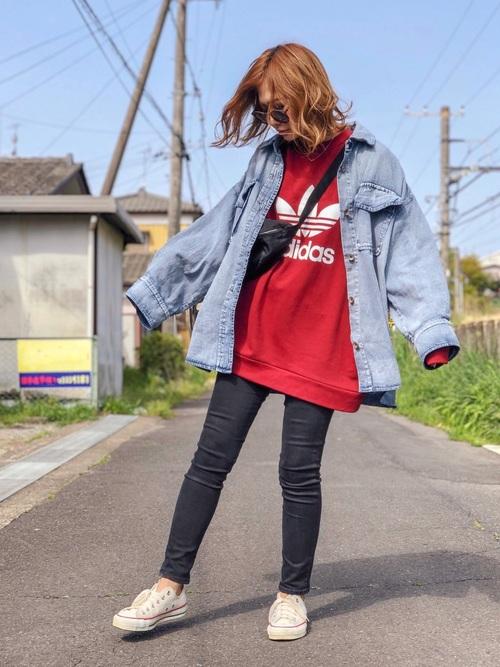 赤スウェットトレーナーに黒デニムスキニーパンツを履いた女性
