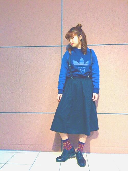 青スウェットトレーナーにAラインフレアスカートを履いた女性