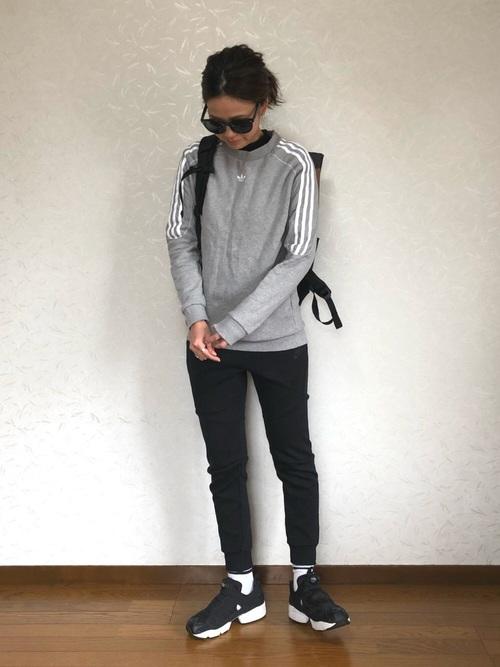 グレースウェットトレーナーに黒ジョガーパンツを履いた女性