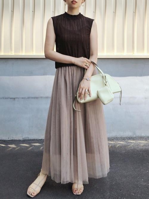 ブラウンチュールシースルーロングスカートにブラウンレースTシャツを着た女性