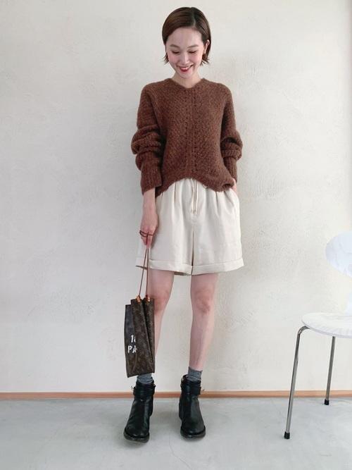 ブラウンブークレニットと白ツータック短パンに黒ショートブーツを履いた女性