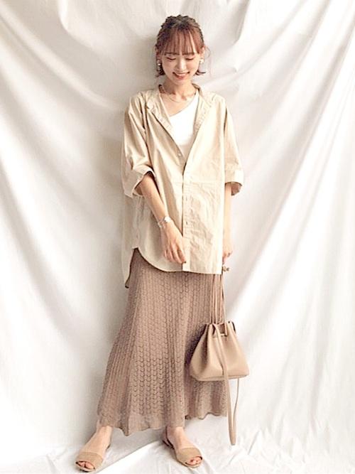 ベージュバンドカラー半袖シャツと白アシンメトリータンクトップとブラウンかぎ編みフレアスカートの夏コーデの女性
