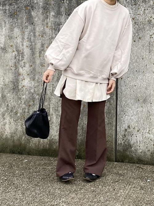 ベージュサイドスリットシャツとベージュバルーンスリーブスウェットとブラウンフレアパンツの冬コーデの女性