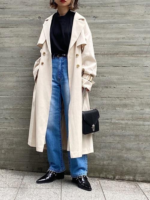 黒ハイネックボリュームロンTとベージュルーズトレンチコートとストレートデニムパンツの冬コーデの女性