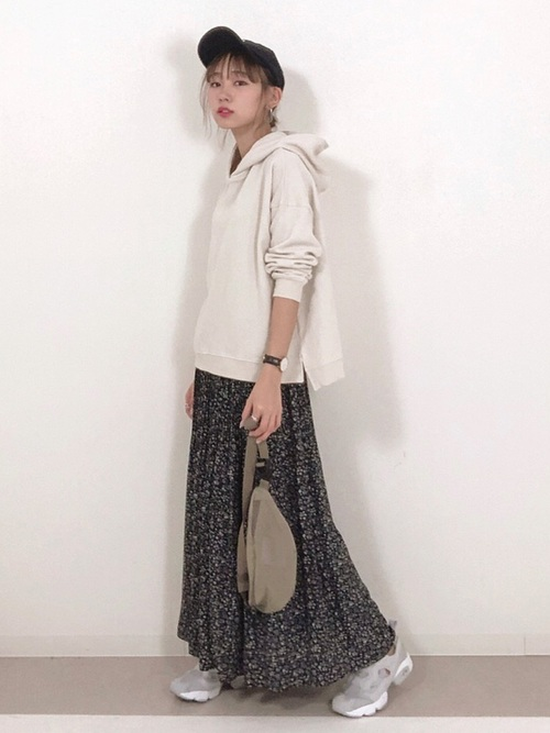 パーカーとスカートに黒キャップという元気な印象のコーデ
