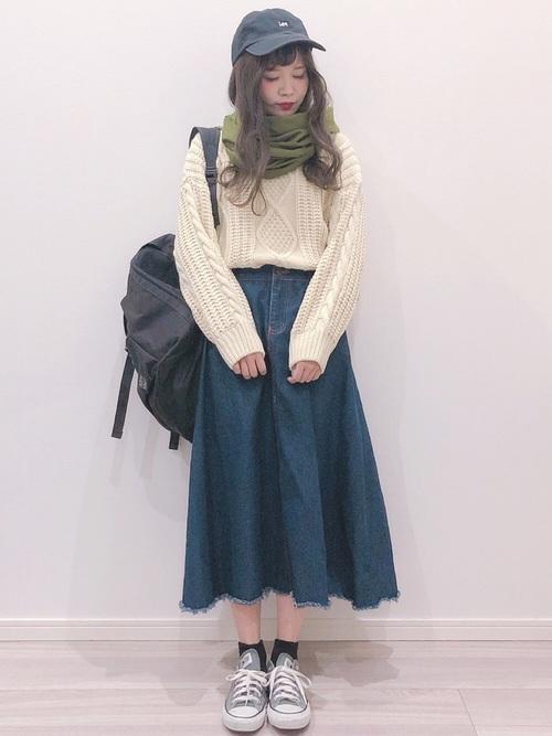 オーバーサイズのセーターとデニムスカートに黒キャップを合わせる女子コーデ