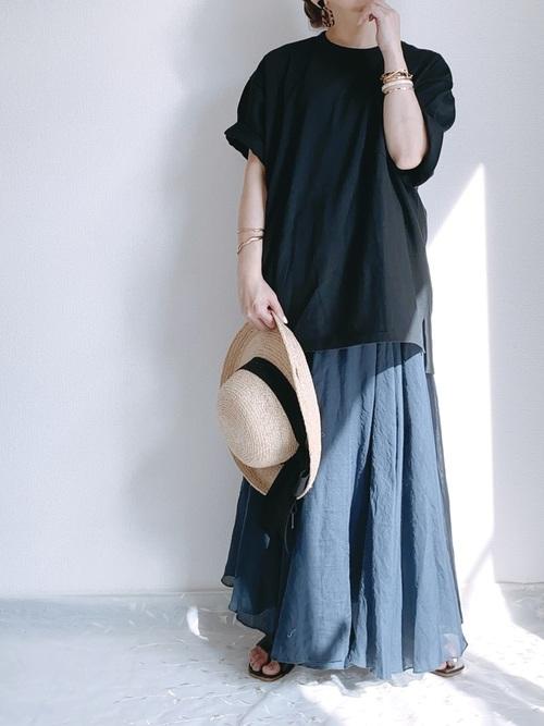 黒ビッグシルエットポケットTシャツと紺フレアボリュームロングスカートにリボン付麦わら帽子を持った女性