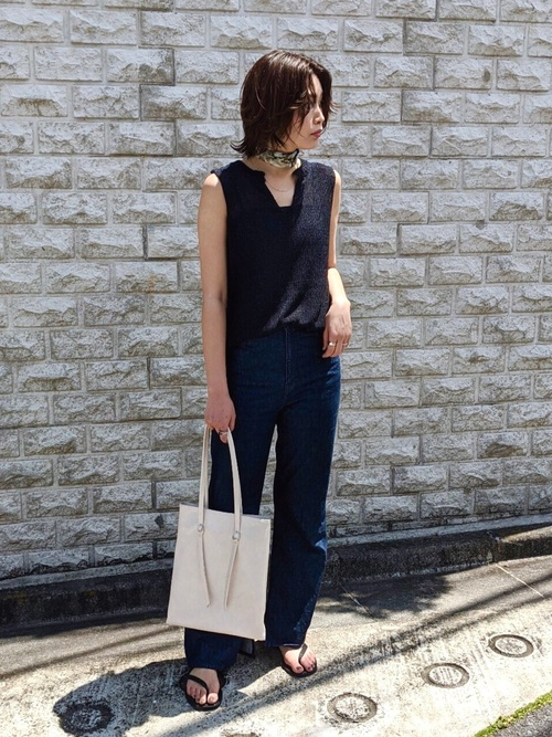 黒ノースリーブニットと紺スリットデニムパンツに白レザーライクトートバッグを持った女性