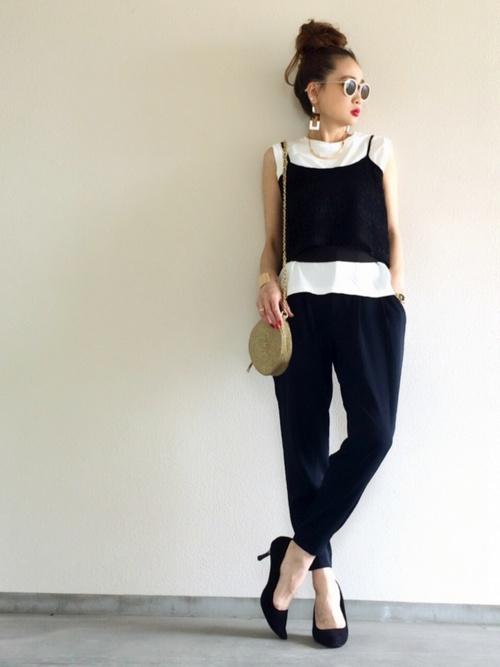 黒キャミソールと紺ジョガーパンツに黒ポインテッドトゥパンプスを履いた女性