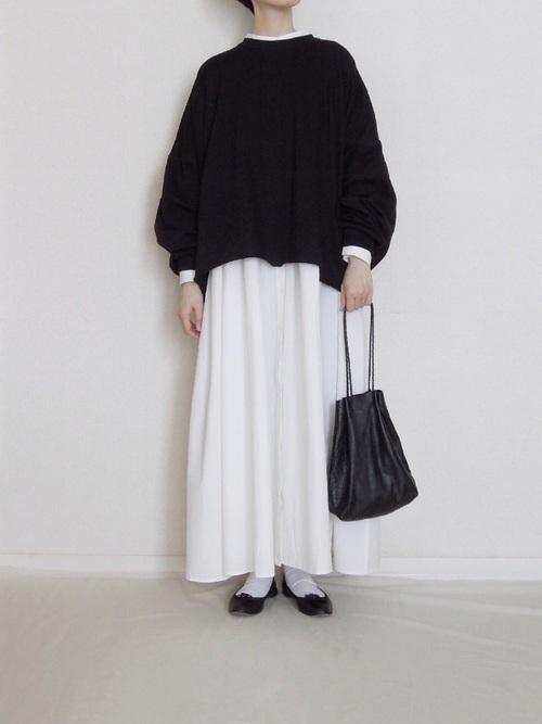 ブラックオーバーサイズスウェットと白ガウンワンピースに黒バレエパンプスを履いた女性