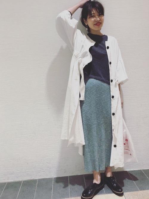 白ガウンワンピースとグレークルーネックカットソーにグリーンメランジニットタイトスカートを履いた女性